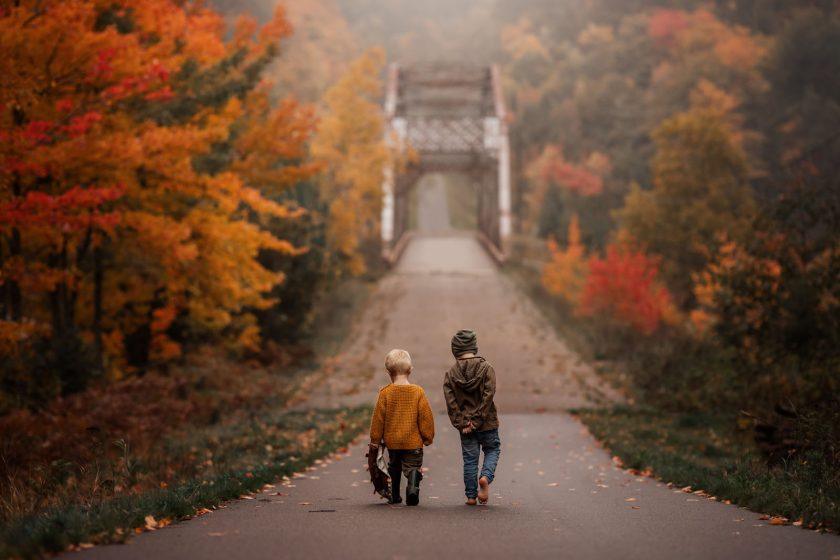 megloeks_image1 two small boys walking along path toward bridge with colorful autumn trees fall activities by meg loeks