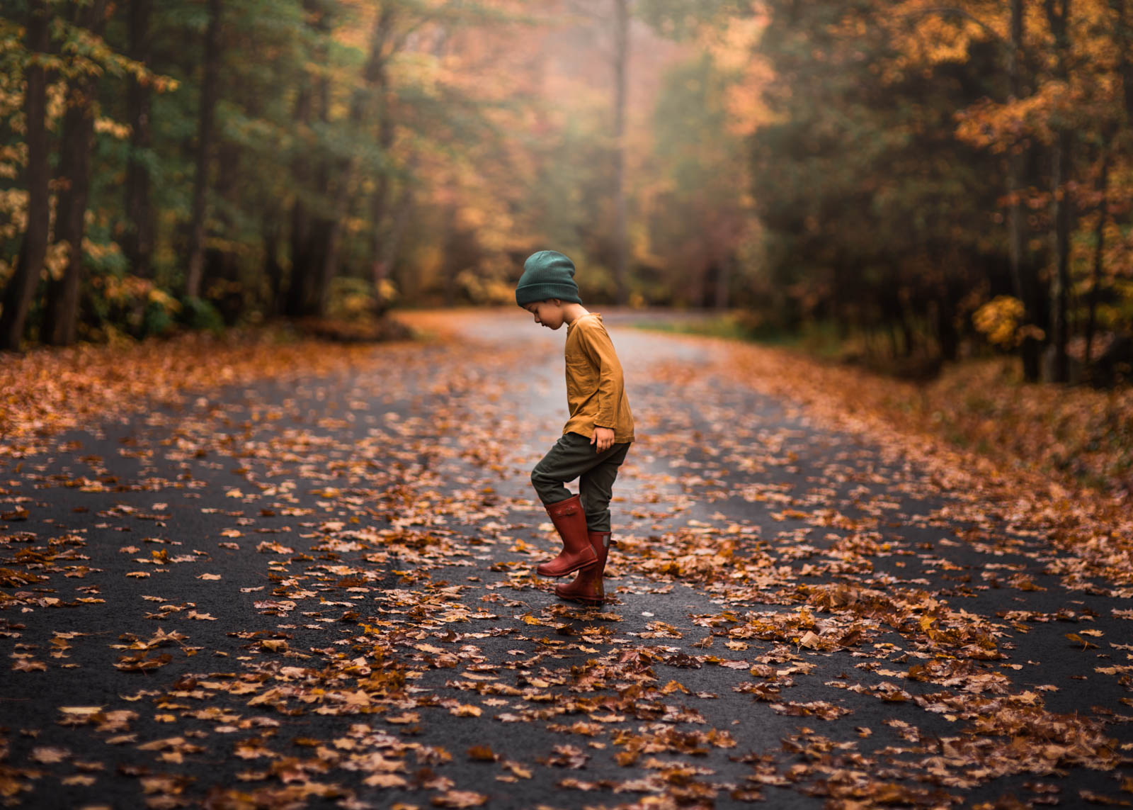 photographing fall color boy in boots and hat on trail with leaves on ground sarah gupta