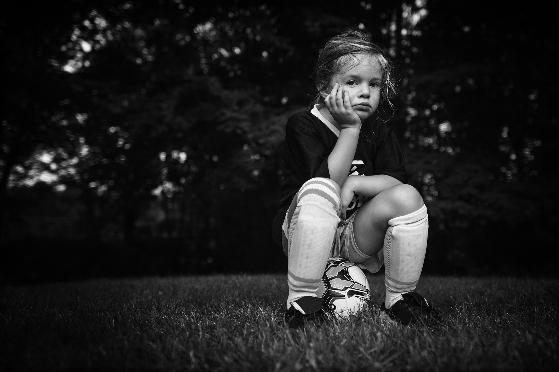 photographing kids sports black and white photo of a girl sitting on a soccer ball by kellie bieser