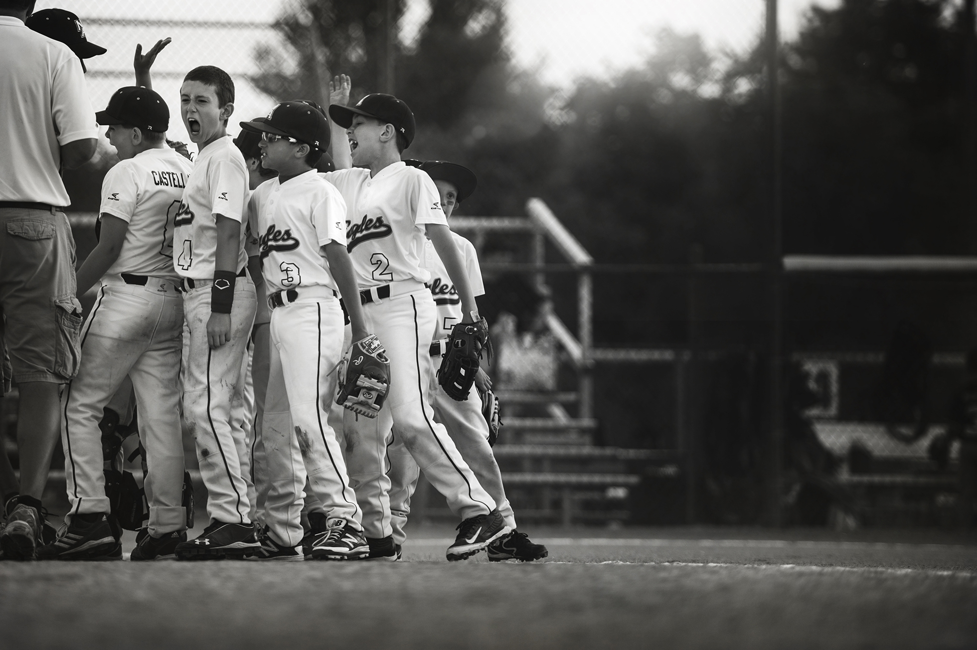 photographing kids sports black and white photo of boys baseball team in huddle cheering by kellie bieser