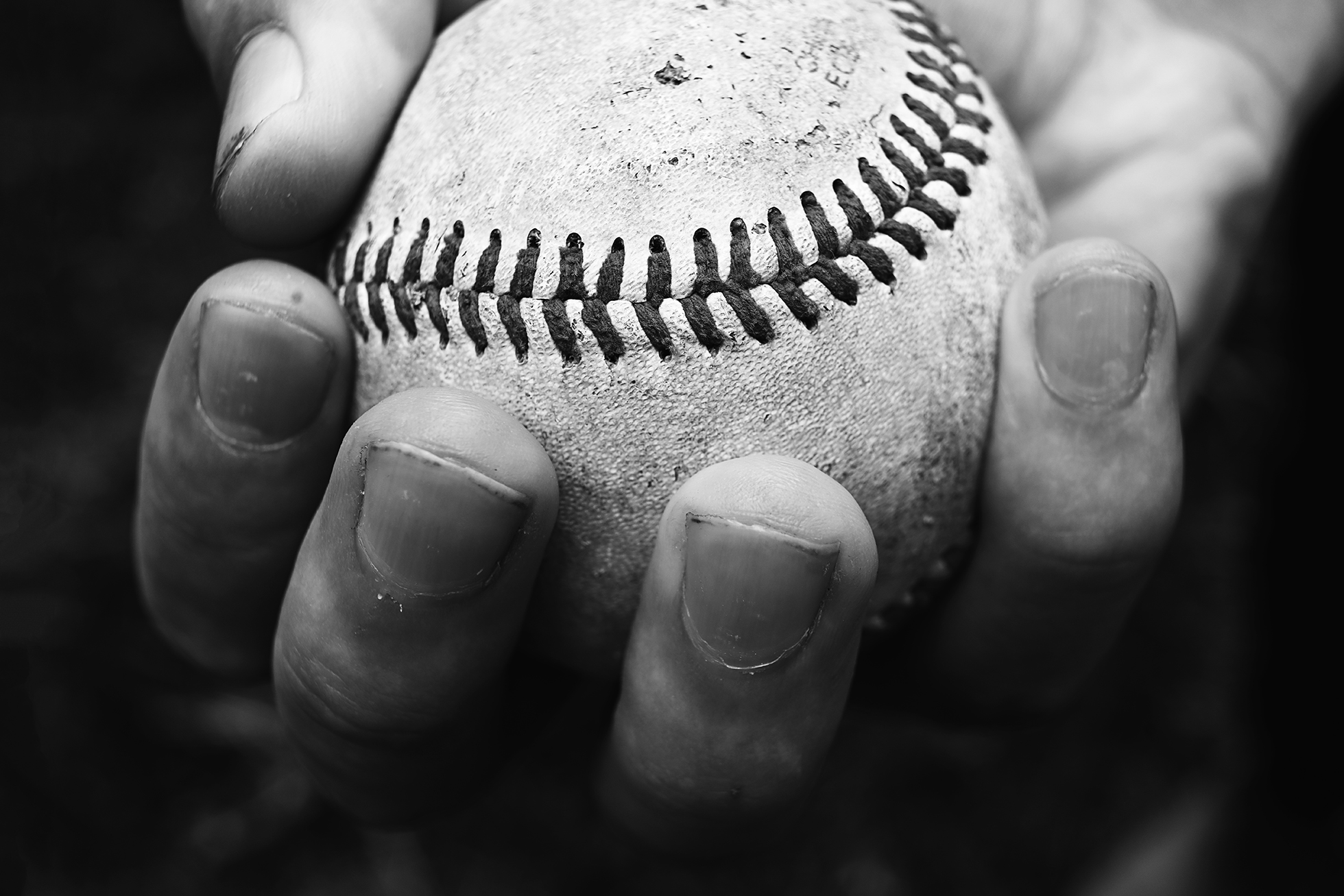 photographing kids sports black and white photo of hand holding baseball details by kellie bieser