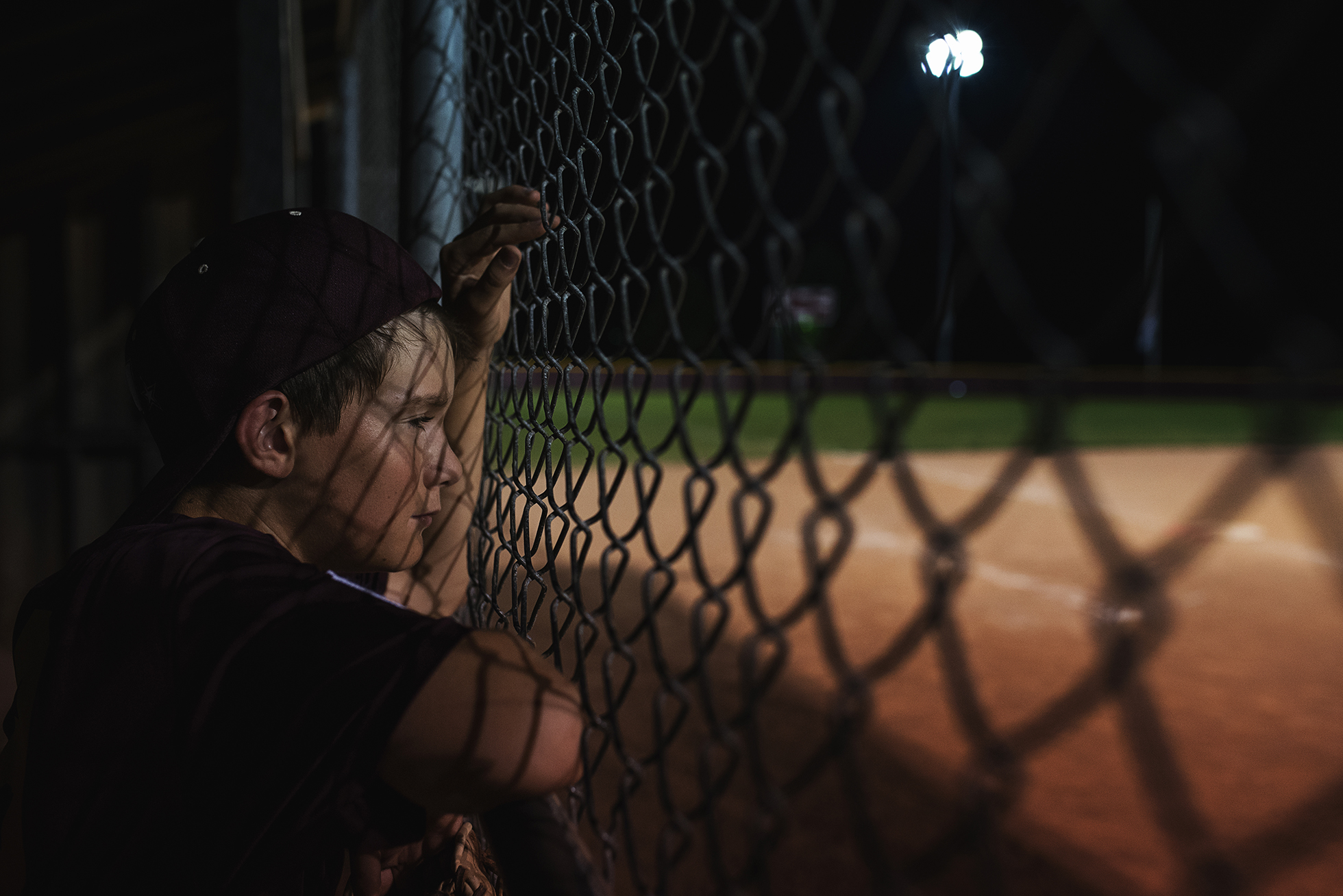 photographing kids sports boy at fence in dugout watching night game by kellie bieser