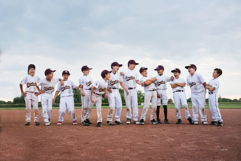 photographing kids sports boys baseball team laughing on field by kelliebieser
