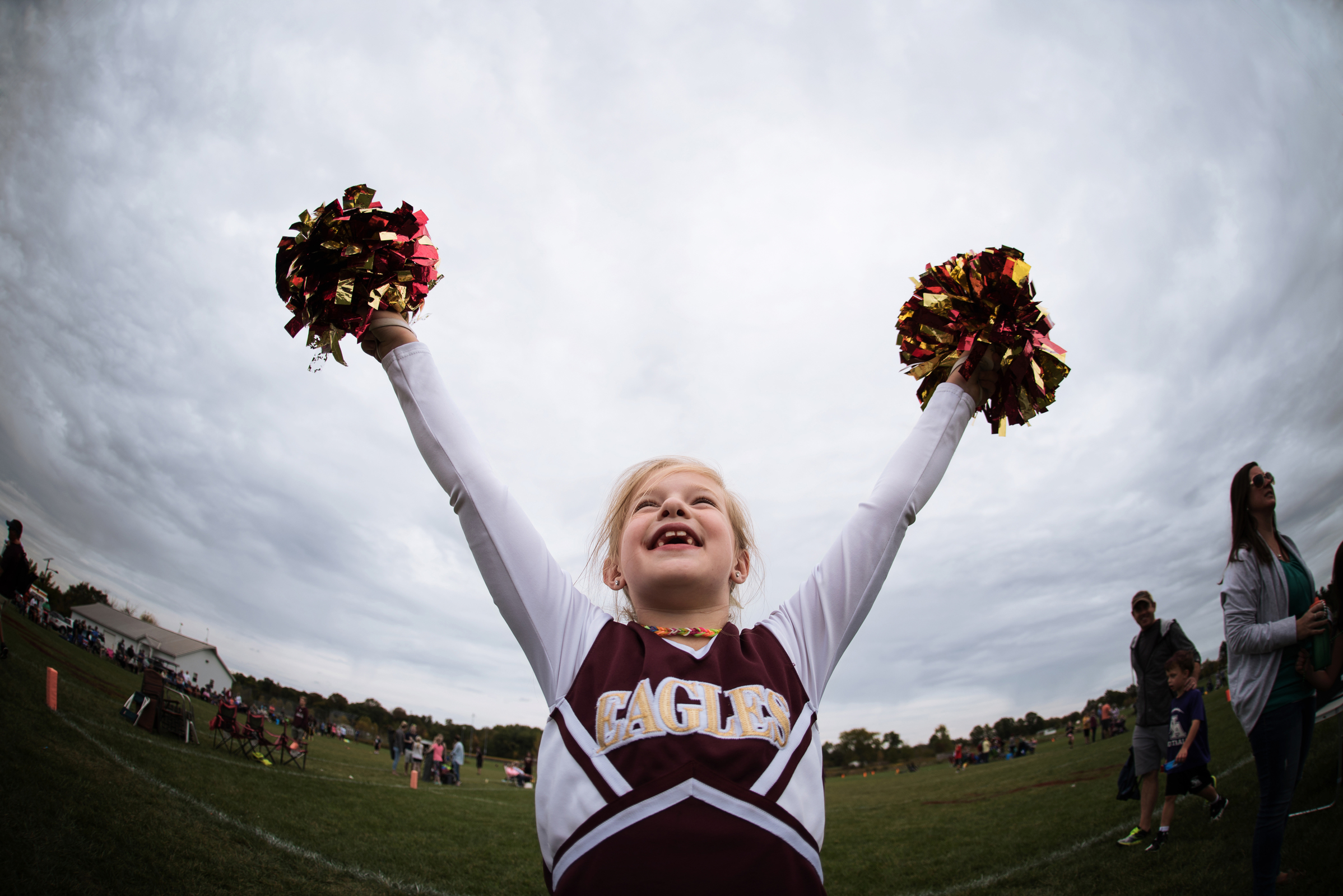 photographing kids sports girl with pom poms cheerleader by kellie bieser