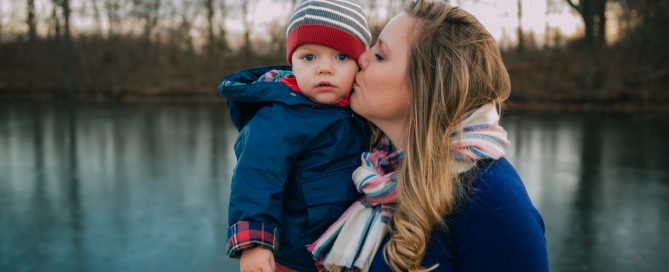 mother kissing child in hat on winter day