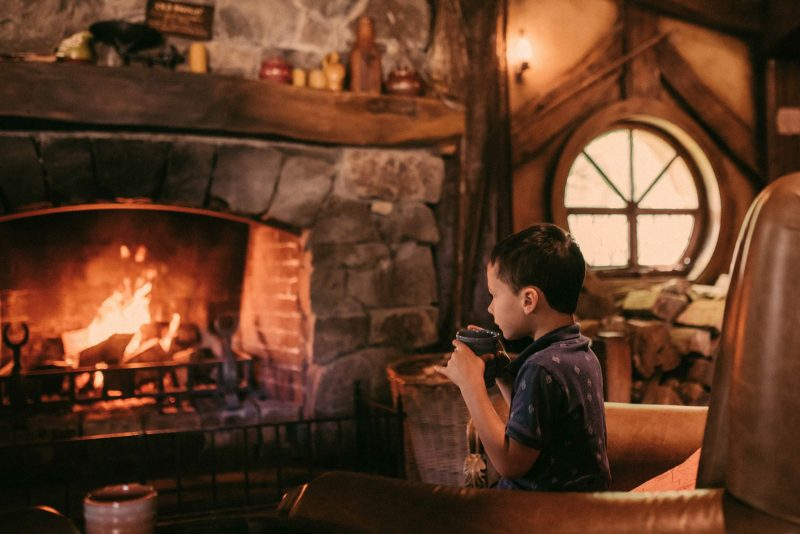how-to-speed-up-workflow-boy with mug sitting in front of fire by-Olga Levien-2